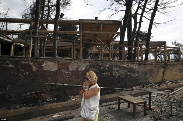 A woman reacts with horror as she surveys the scene of a burnt out property in the resort of Mati, to the east of Athens