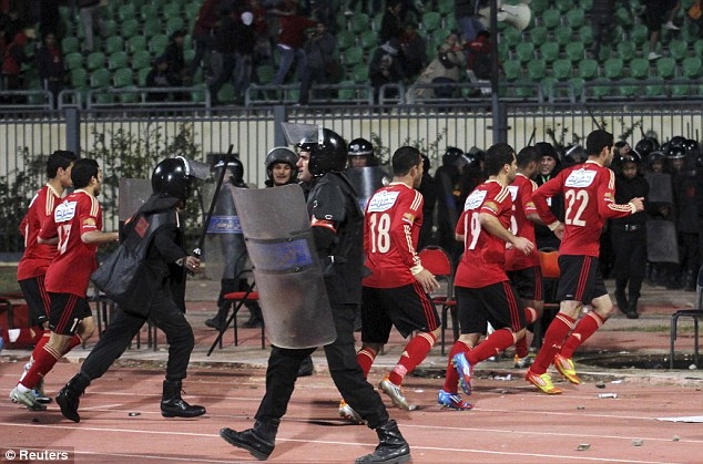 Running for cover: Players involved in a tie between Al-Masry and Al-Ahly had to flee Port Said Stadium during the riots which claimed 74 lives