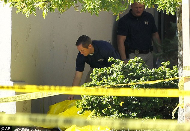 Horror: Gilbert police officers walk inside the police tape outside a crime scene on Wednesday after four people, including a toddler, were fatally shot