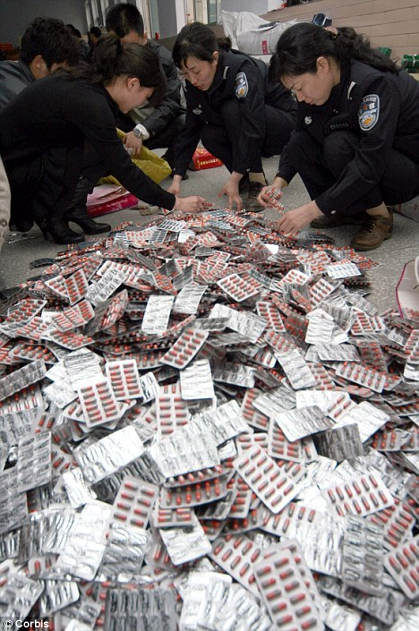 Crackdown: Chinese officials, pictured confiscating thousands of illegal tablets, say they will clampdown on the massive herbal medicine industry which has seen dangerous bacteria an human remains added to seized pills