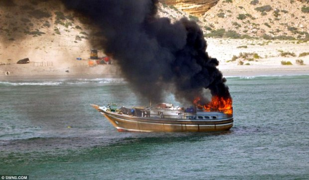 Up in flames: One person on the dhow was killed and 25 others were rescued by the warship after jumping into the ocean to escape the fire on board