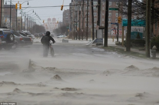 Washed up: A resident pushes a bicycle down a street covered in beach sand due to flooding from Superstorm Sandy in Long Beach, New York