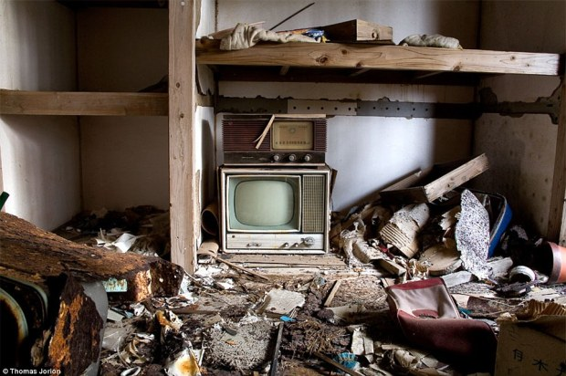Time stood still: A television and radio sit among rotting timber and carpets in what was once a private apartment