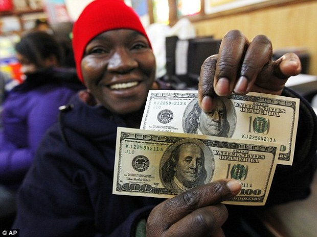 Overjoyed: Charlotte Muhammad holds up two $100 dollar bills handed to her at St. Joseph's Social Service Center in Elizabeth, New Jersey on Thursday