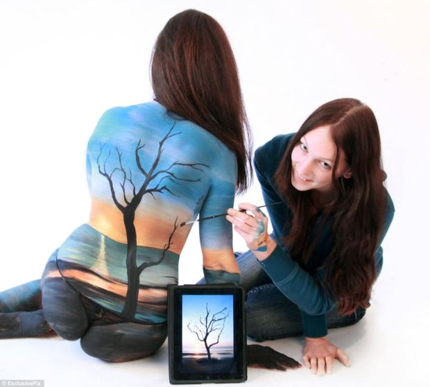Gesine Marwedel gets to work on one of her subjects, this time painting a tree on a beach