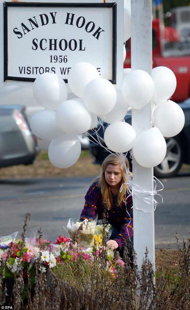 A young woman places flowers at a memorial near the Sandy Hook Elementary School following Friday's shooting that has left at least 28 people dead, 20 of them young children