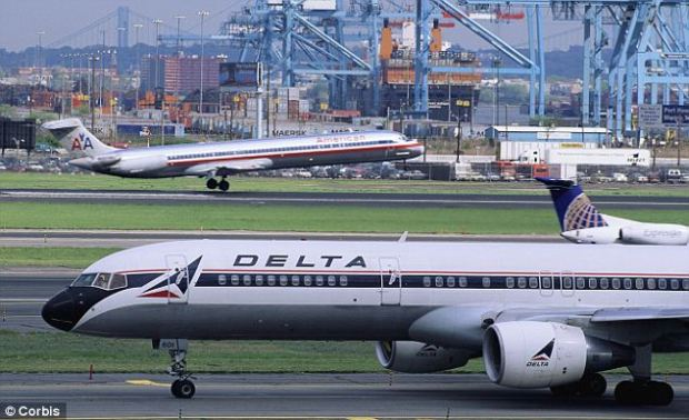 Hoax: Planes taxi and take off at Newark Airport. One man was questioned and searched by police after his wife falsely accused him of plotting to 'blow up' a Delta flight to Paris