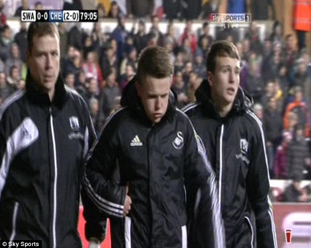 Hurt: The ballboy (centre) is ushered away from the sidelines following the incident with Eden Hazard