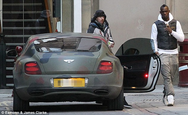 Keeping a low-profile? Mario Balotelli leaves a Manchester store by the back door after a friend drove his Bentley GT around the corner