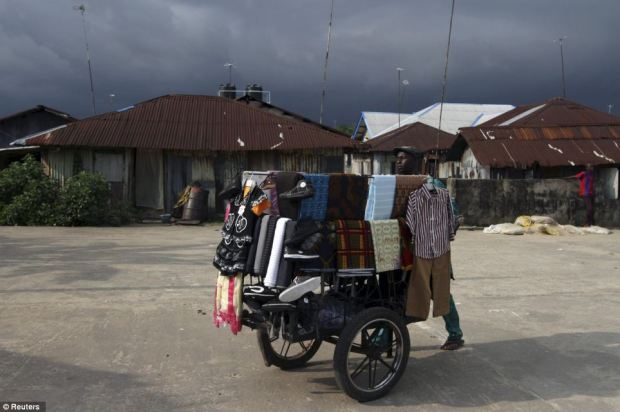 A vendor pushes a cart filled with clothes along a street in the coastal town of Twon Bass
