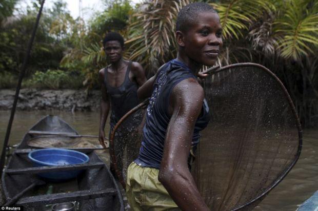 Women fish in a creek near the River Nun in Nigeria's oil state of Bayelsa