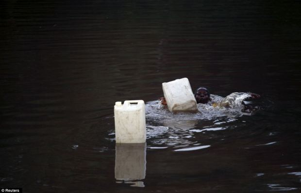 Children play in a polluted river in the Kalaba community in Nigeria's oil state of Bayelsa