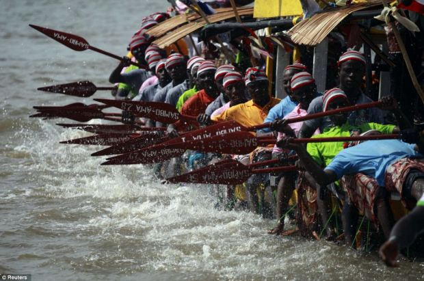 Youths take part in a traditional boat regatta for the burial ceremony of a local chief in the coastal town of Twon Bass