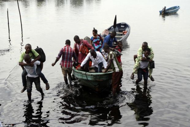 Boat guides carry people through polluted water as passengers disembark from a speedboat at the shore of Bodo creek in Ogoniland