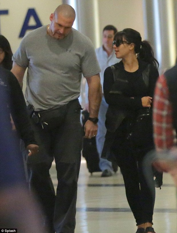 Safety first: Kim chats to Kanye's Head of Security as she walks through the airport