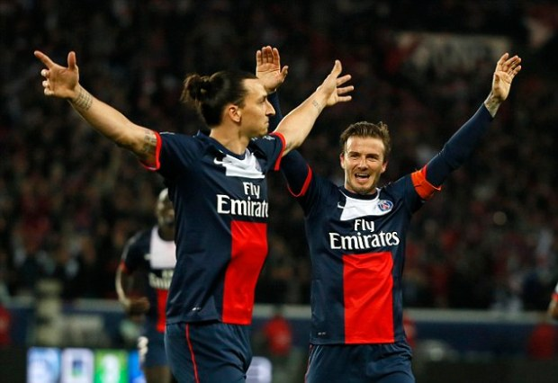 Bowing out on top: Beckham celebrates with teammate Zlatan Ibrahimovic as he scores a third goal for PSG
