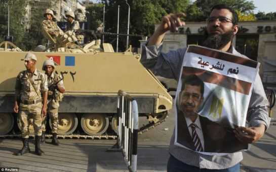 Supporter: Army soldiers stand guard near a supporter of ousted President Mohamed Mursi at Cairo University in Giza, on the outskirts of Cairo