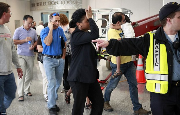 Long day: A woman reacts as a group of people are escorted from the Reflection Room at San Francisco International Airport