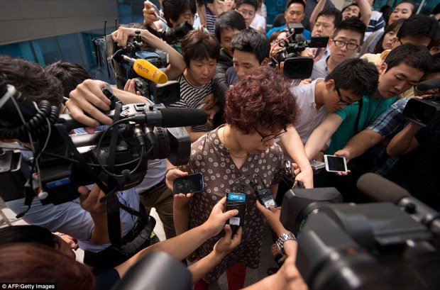Frenzy: A woman (center), believed to be the mother of a victim an Asiana Airlines aircraft crash in San Francisco, is surrounded by members of the media in the lobby of the company's headquarters in Seoul