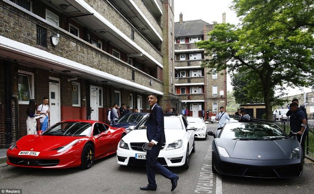 High life: Aminul Mishu Alam, 16, walks past cars parked on a Tower Hamlets council estate - one of Britain's most deprived areas