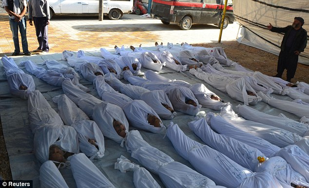 Slaughter: Syrian activists inspect the bodies of people they say were killed by nerve gas in Damascus