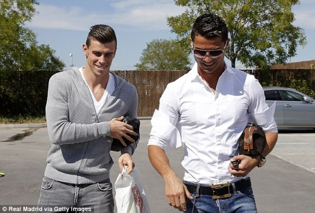 Welcome aboard: Bale and Ronaldo share a smile as they arrive at Real Madrid's training ground