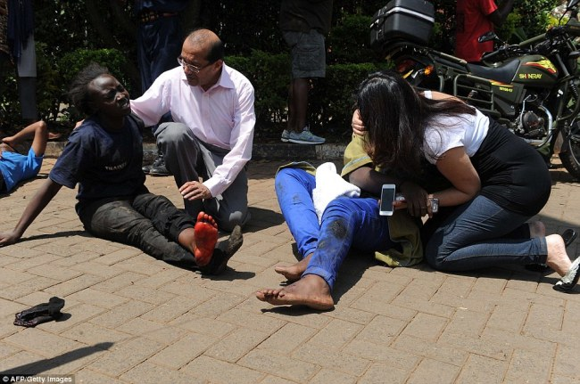 Devastating: Injured people receive assistance from bypassers at the scene of the shooting