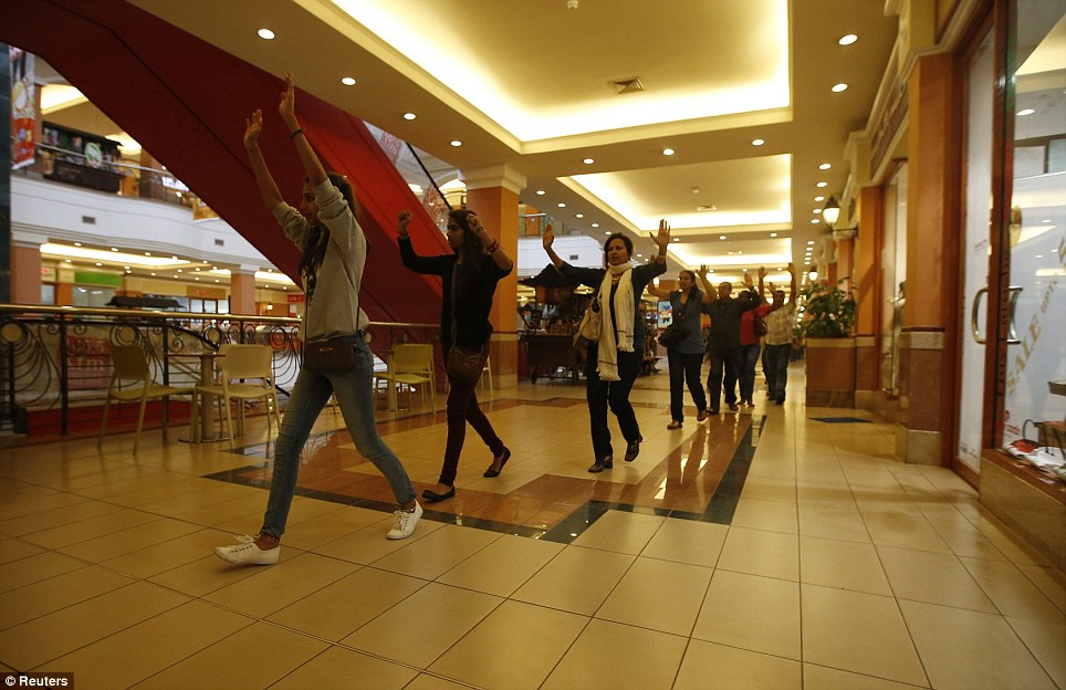 Safety: Shoppers and shop assistants raise their hands as they are escorted out by armed police
