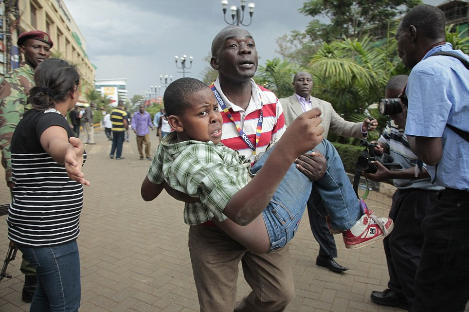 Help: A man carries a boy away from the scene of the carnage earlier today