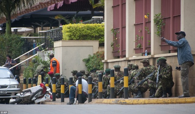 Laying siege: Armed police crouch down and take position during a gun battle with Islamic terrorists at the Westgate Mall in Nairobi, Kenya on Saturday