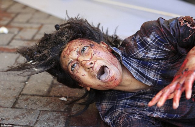 Desperation: An injured woman, whose face and clothes are drenched in blood, lies on the ground outside the shopping mall screaming for help