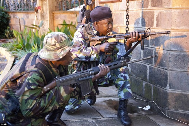 Siege: Kenya security personnel take cover outside the Westgate Mall after shooting started inside the mall early Monday morning, Sept. 23, 2013