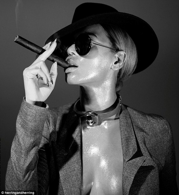 Smoking hot! Beyonce puffs on a cigar, sporting a black hat, sunglasses and collar in another image