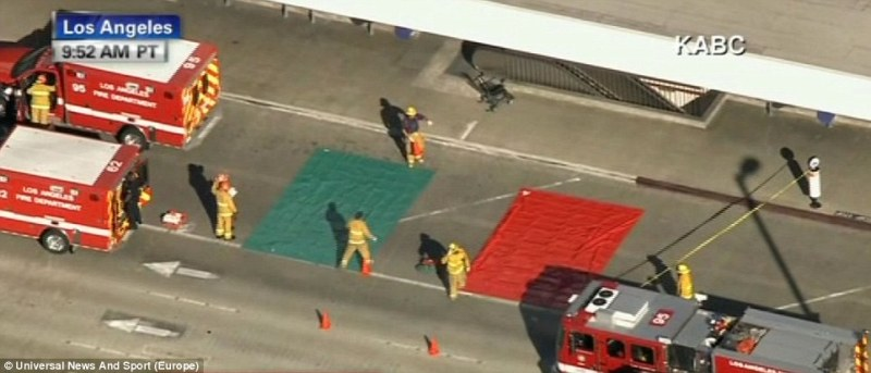 Fire crews spread triage mats in front of LAX following reports of multiple injuries inside LAX after a gunman opened fire