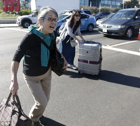 Passengers pictured at LAX today following the fatal shooting at Terminal 3