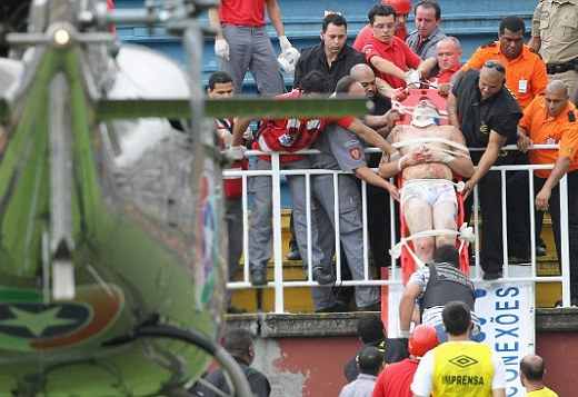 An injured fan is carried on a stretcher towards the helicopter after violent clashes between the supporters