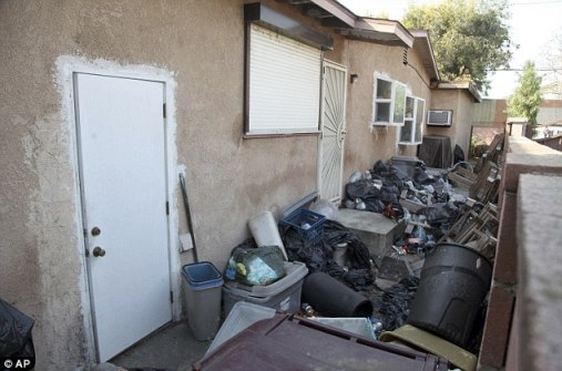 Loads of trash is shown stacked against the home of William Buchman on Wednesday