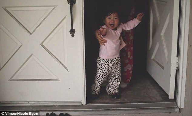 Not ready: The cute toddler cries after being carried back inside her house