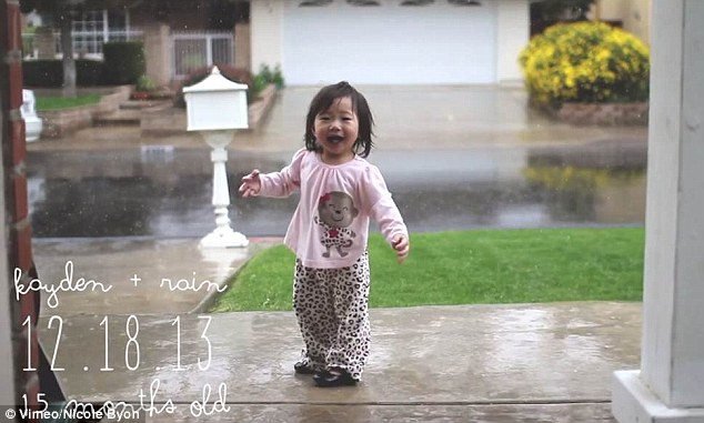 Rainy day: Kayden looks shocked as she feels rain for the first time outside her California home