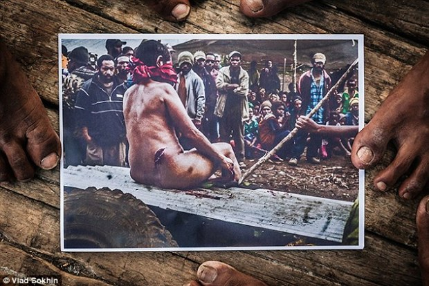 Law of the jungle: Accused of being a witch this woman was stripped, beaten, slashed, blindfolded and placed 'on trial' on a piece of roofing iron in this snapshot (above) captured by a villager. Days later she was tied to a stake and tortured with branding irons amid a frenzied crowd which chanted 'kolim nem' (call the name) of the so-called witch to save her own life