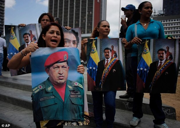 Pro-government demonstrators: Supporters of Venezuela's President Nicolas Maduro, hold posters of him and of late Venezuelan President Hugo Chavez during a demonstration outside the Palace of justice in Caracas, Venezuela