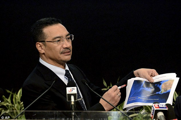 Breakthrough: Malaysia's Defense Minister and acting Transport Minister Hishammuddin Hussein shows a printout of the latest satellite image of objects that might be from the missing Malaysia Airlines plane