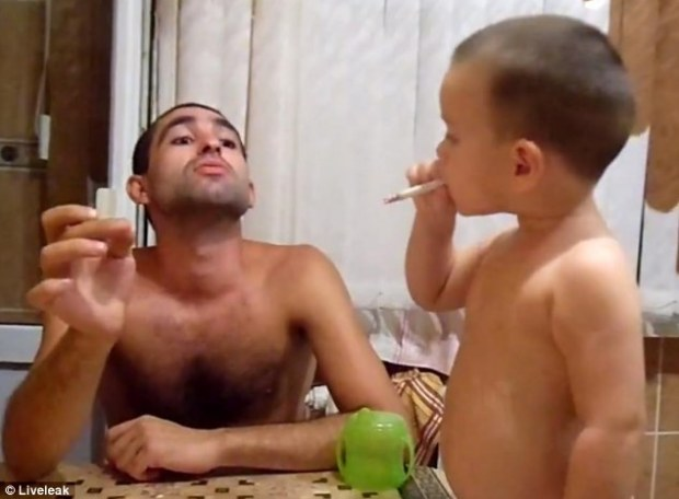 Father of the year: The young boy inhales from the cigarette, clearly following in his shirtless father's footsteps
