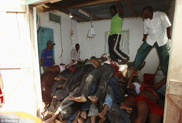 Shocking: Residents look at slain bodies of people killed when unidentified gunmen attacked the coastal Kenyan town of Mpeketoni - the latest in a string of Islamic militant attacks across two continents that have shocked the world
