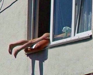 A nude woman sunbathing in the Austrian capital Vienna caused snarl ups on a major road when she positioned her naked body out of a window to get the maximum out of the sun's rays