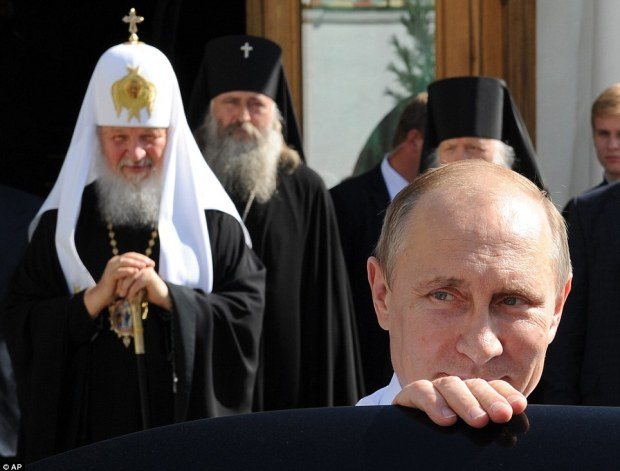 Behind it all? Vladimir Putin, pictured with Orthodox church Patriarch Kirill at a religious celebration yesterday, is under international pressure