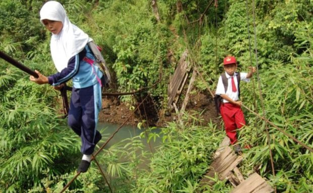Close to collapse: This bridge on the island of Sumatra was destroyed by heavy rain. The determined pupils from the Batu Busuk village who cross it every day then have to walk a further seven miles through dense forest to their school in the town of Padang
