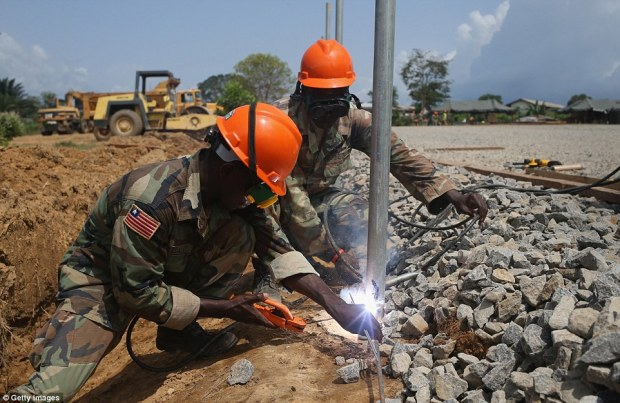 At work: Soldiers from the Liberian Army's 1st Engineer Company are seen welding a fencepost at the site of an Ebola treatment center