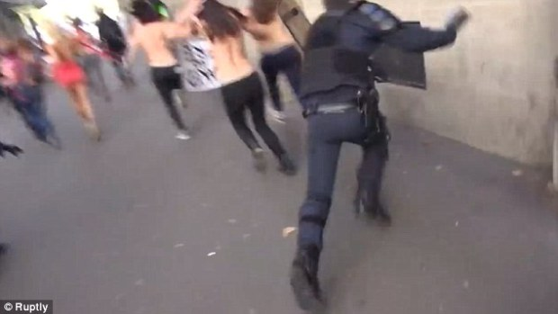 A French policeman face-plants into a wall after getting distracted by topless Femen protesters in Paris