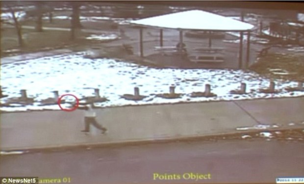 Surveillance footage shows 12-year-old Tamir Rice raising and pointing his replica gun as he walks through a park in Cleveland, Ohio on Saturday. Just moments later, he was fatally shot by police